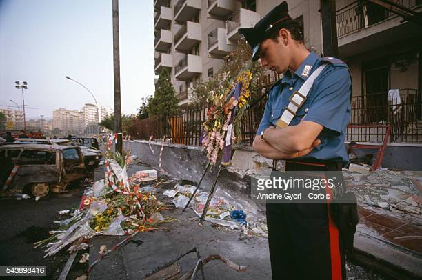 A young police officer looks down at the crime scene next to bouquets and wreaths left at a makeshift memorial for antiMafia judge Paolo Borsellino...