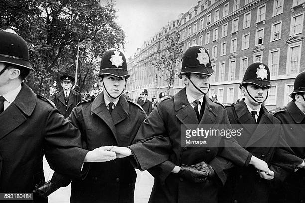 Young policemen lock arms as they prepare to take the strain for large crowds in Grosvenor Square , London at a mass Anti Vietnam war rally. 27th...