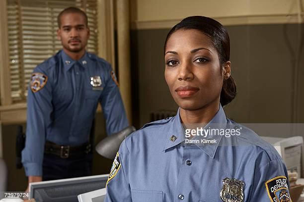 young policewoman and young policeman in office, portrait - forze di polizia foto e immagini stock