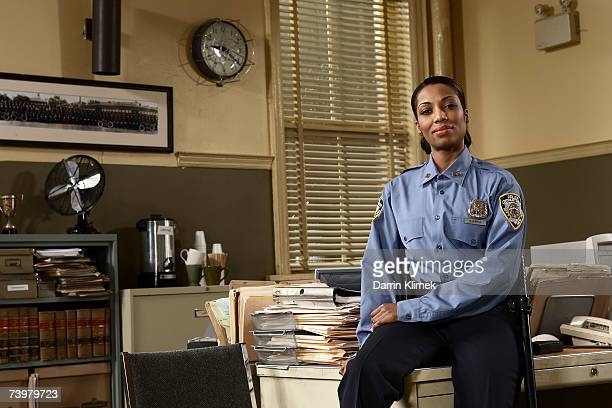 Young policewoman sitting on desk, portrait