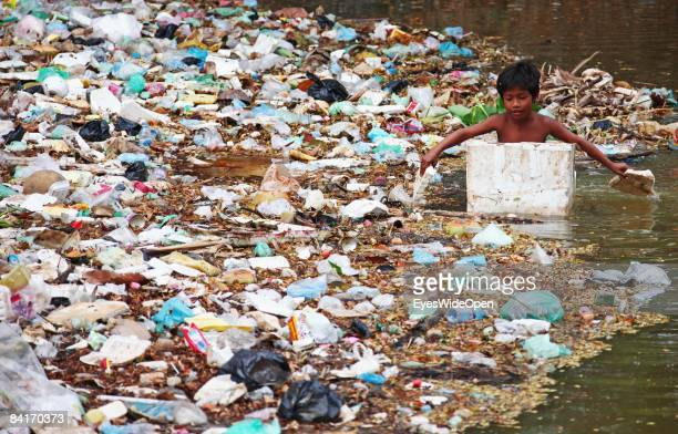A young poor boy rowing in his boat made of styropor is collecting cans and plastic bottles out of the garbage swimming in the Siem Reap River near...