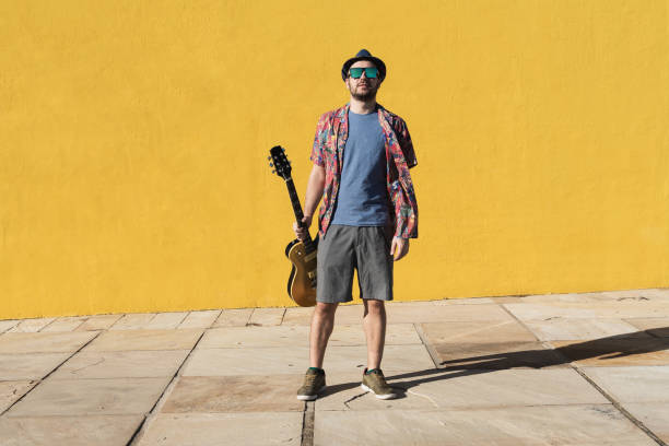Young pop musician with electric guitar in a cool attitude. Summer happy pop rock music