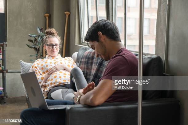 young pregnant couple working from home - massage couple photos et images de collection