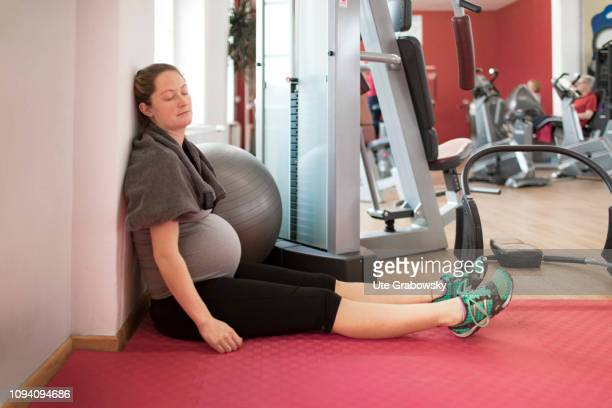 Young pregnant woman after the training in a gym on January 24 2019 in Bonn Germany The woman is eight months pregnant is relaxing