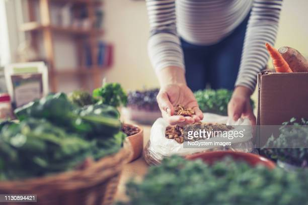 young pregnant woman buying healthy food at health food shop - health food shop stock pictures, royalty-free photos & images
