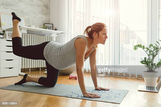 Young Pregnant Woman Exercise In Her Living Room.