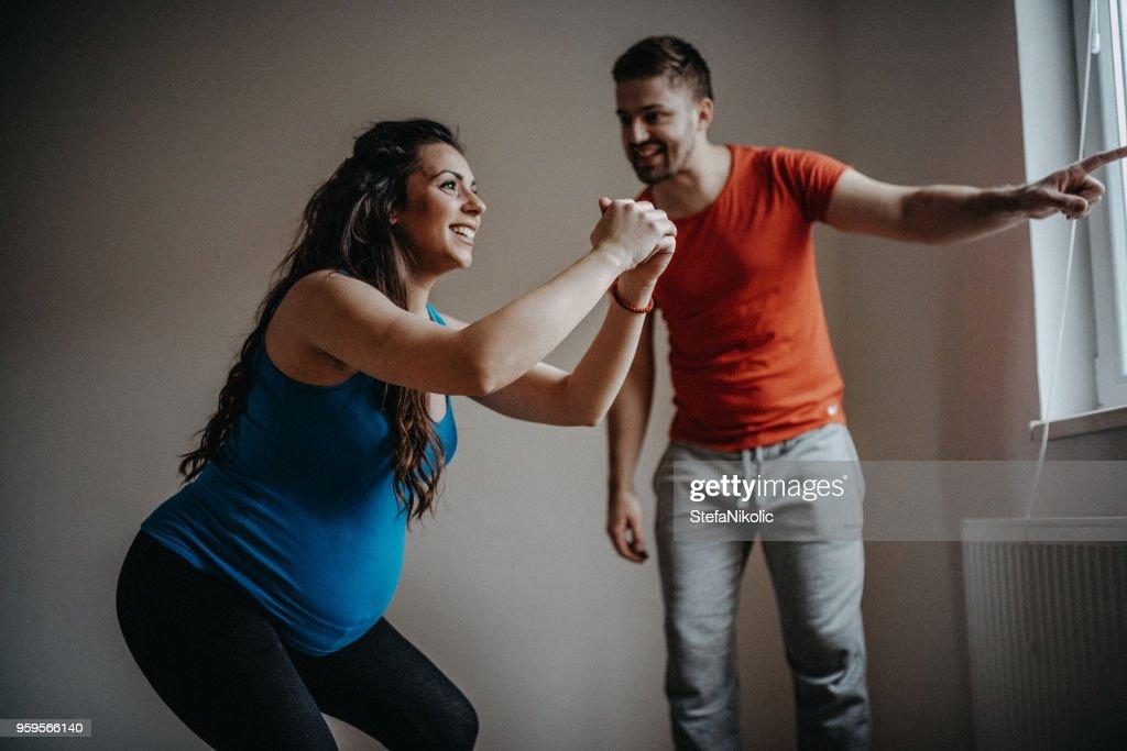Junge schwangere Frau Übung In ihr Wohnzimmer mit ihrem Ehemann : Stock-Foto