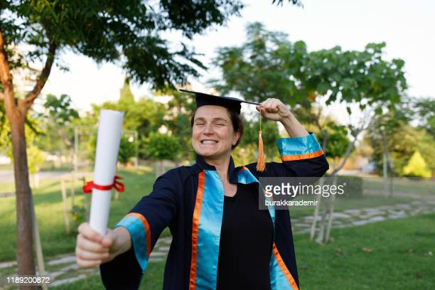 young pregnant woman got master's degree diploma - master's degree stock pictures, royalty-free photos & images