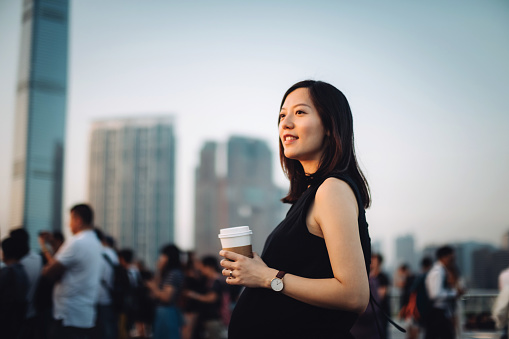 Young pregnant woman having coffee and relaxing in city, looking towards the beautiful sky at sunset - gettyimageskorea