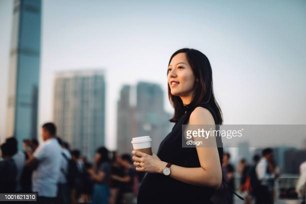 young pregnant woman having coffee and relaxing in city, looking towards the beautiful sky at sunset - pregnant coffee stock pictures, royalty-free photos & images