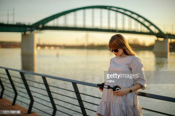 young pregnant woman holding headphones on her belly outdoors - miljko stock pictures, royalty-free photos & images