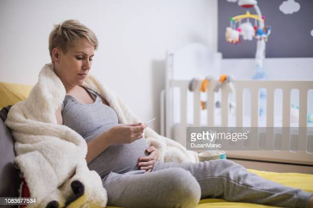 Young pregnant woman in bed with a thermometer. Sick with the flu or a cold.