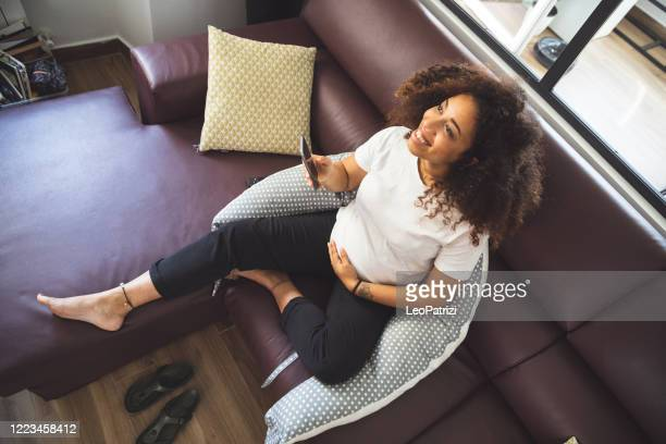 young pregnant woman in her house relaxing - avoidance stock pictures, royalty-free photos & images