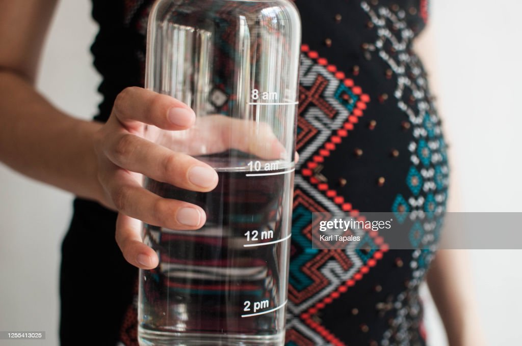 A young pregnant woman is holding a reusable water bottle with time stamp : Stock Photo