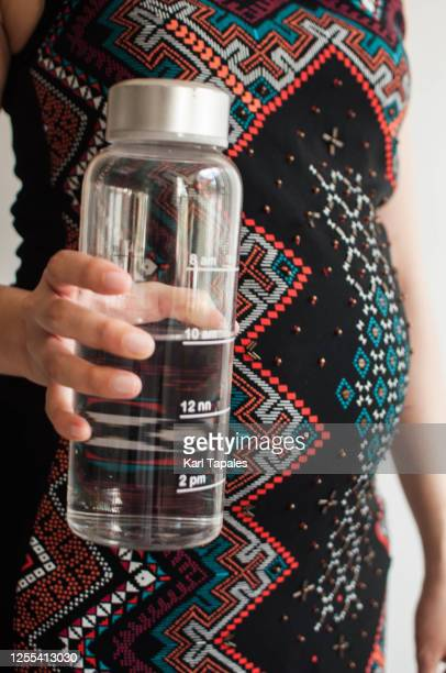 a young pregnant woman is holding a reusable water bottle with time stamp - filipino ethnicity and female not male fotografías e imágenes de stock