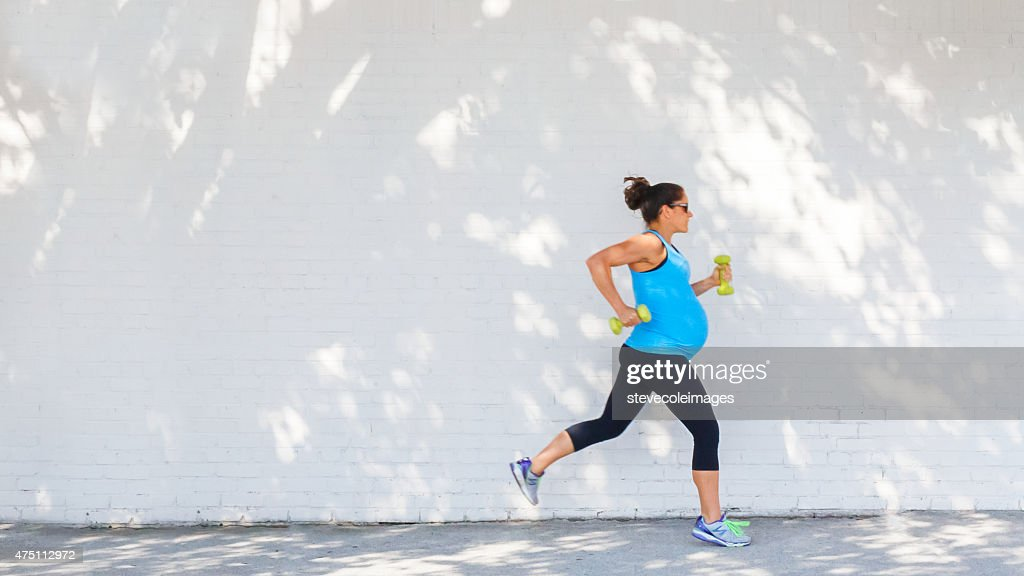 Young pregnant woman jogging down sidewalk in city. : Stock Photo