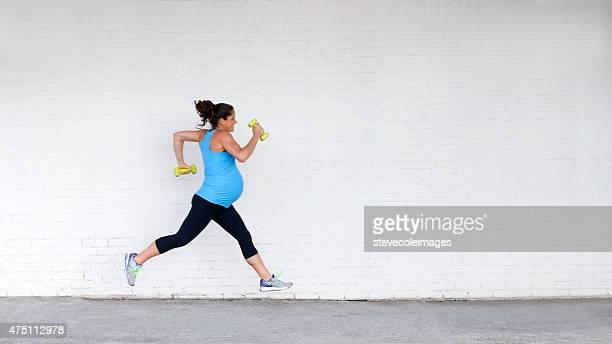Jeune femme enceinte heureuse, jogging le long de la rue dans la ville.