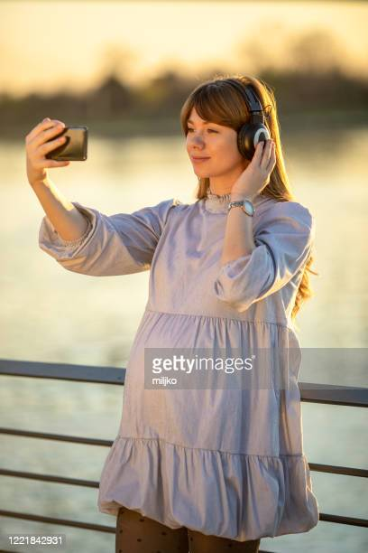 young pregnant woman listening music outdoors at sunset - miljko stock pictures, royalty-free photos & images
