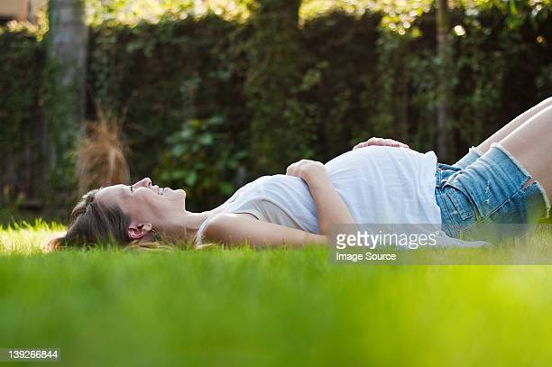 Young pregnant woman lying on grass