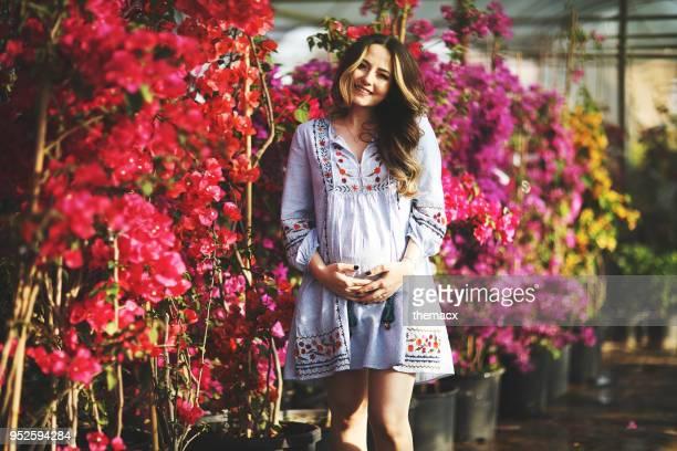 jeune femme enceinte sur jardin fleuri - robe photos et images de collection