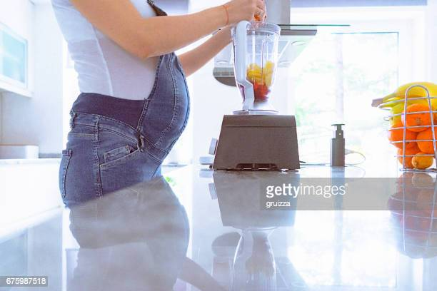 Young pregnant woman prepares fruit for smoothie at home in the morning