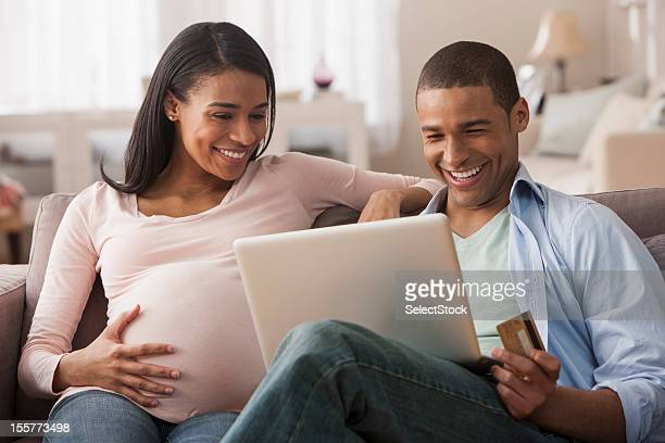Young pregnant woman sitting with husband making online purchase