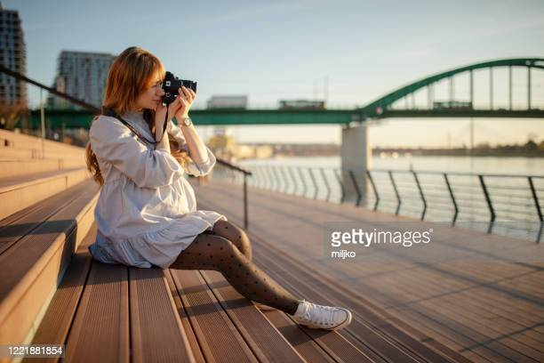 young pregnant woman taking photo outdoors - miljko stock pictures, royalty-free photos & images