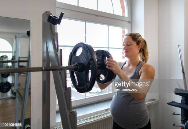 Young pregnant woman training in a gym on January 24 2019 in Bonn Germany The woman is eight months pregnant and is doing strength training