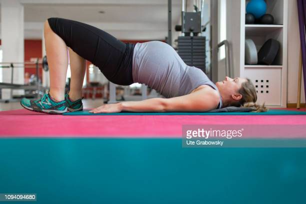 Young pregnant woman training in a gym on January 24 2019 in Bonn Germany The woman is eight months pregnant and is doing gymnastics