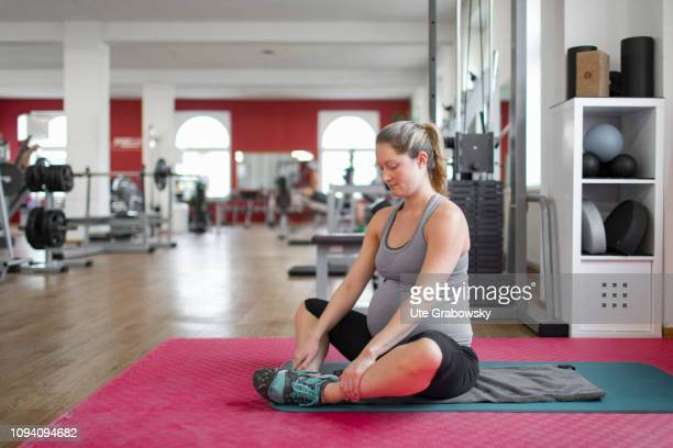 Young pregnant woman training in a gym on January 24 2019 in Bonn Germany The woman is eight months pregnant and is doing stretching