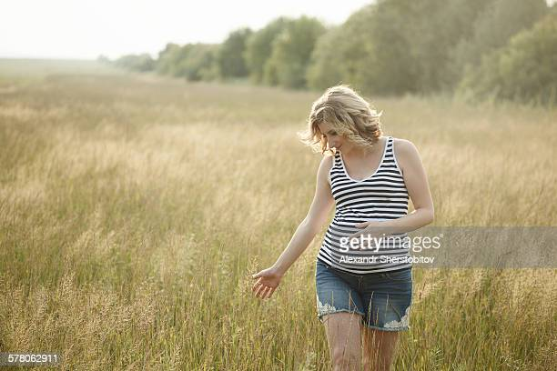 Young pregnant woman walking by the field