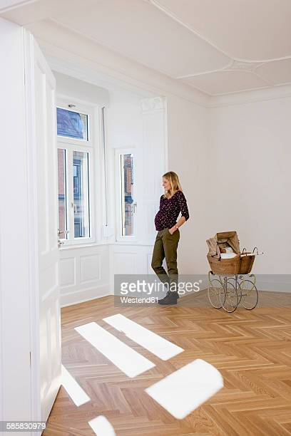 Young pregnant woman with pram in an empty room looking out of window