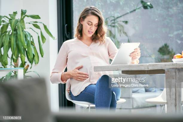 young pregnant women in contemporary house - worried stock pictures, royalty-free photos & images