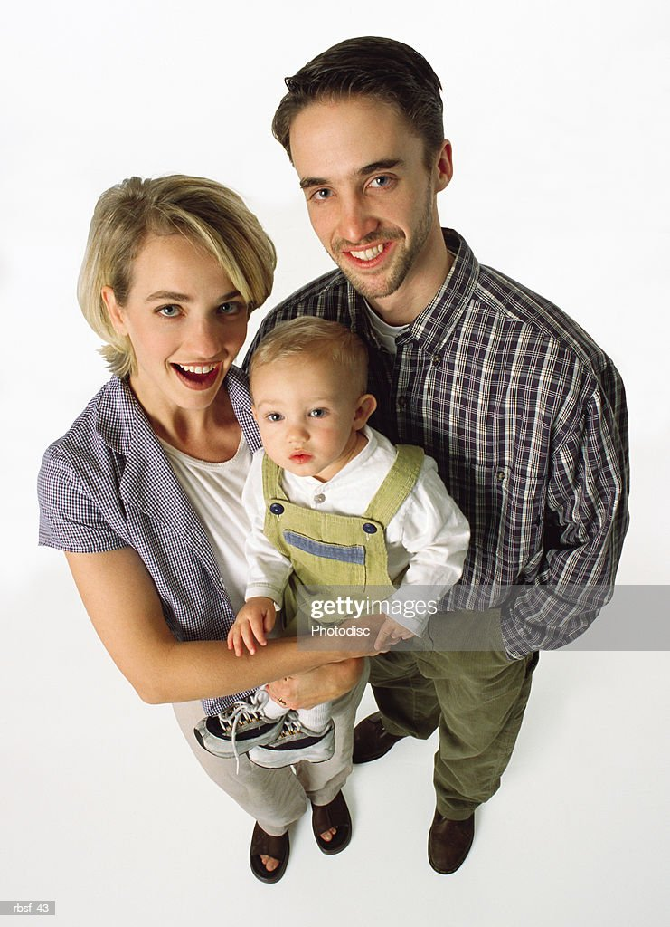 young preppy couple standing with laughing mom holding infant in khaki overalls : Foto de stock
