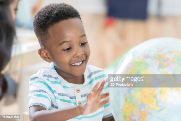 Young preschool age boy studies a globe