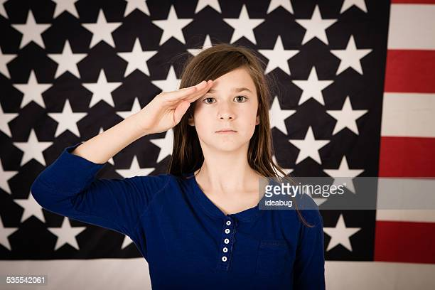 Young Preteen Girl Saluting in Front of American Flag