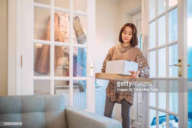 young pretty asian woman receiving home delivered parcels in new house - beautiful people stock pictures, royalty-free photos & images