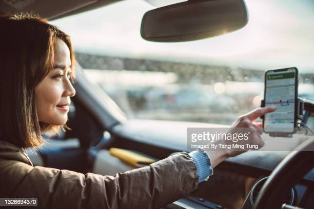 young pretty asian woman using gps navigation in the car - direction stock pictures, royalty-free photos & images