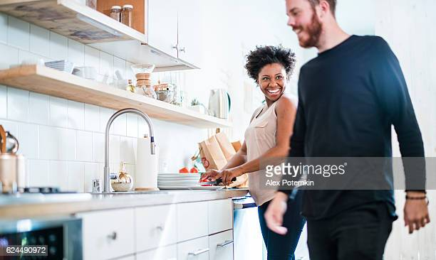 Young pretty black woman make soup in kitchen