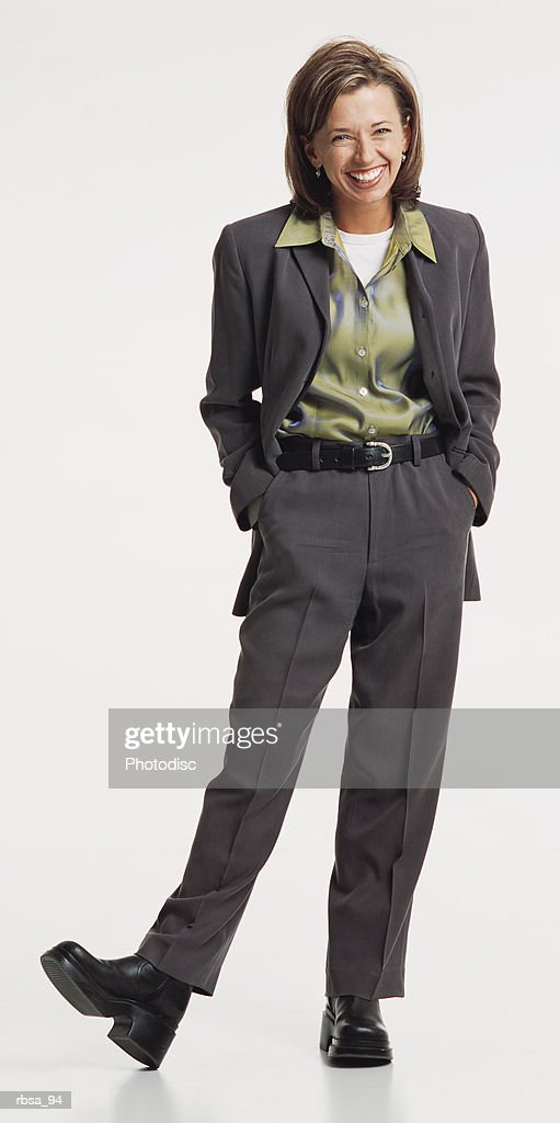 young pretty blonde caucasian adult female wearing a gray pant suir with a green silk blouse stands jauntily with her right heel tipped and the toe of her shoe in the air as she laughs looking at the camera : Foto de stock