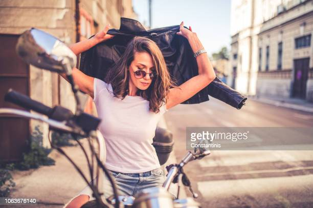 young pretty fashioned girl sitting on her motorcycle - maglietta foto e immagini stock