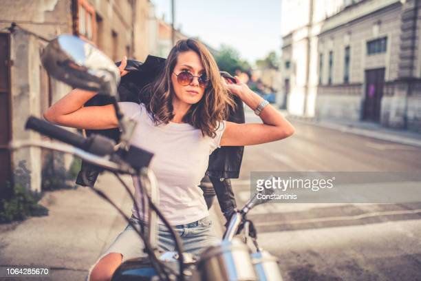 young pretty fashioned girl sitting on her motorcycle - biker jacket stock pictures, royalty-free photos & images