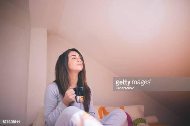 Jolie jeune fille relaxante dans son lit au matin. Elle est jouir et boire du café.