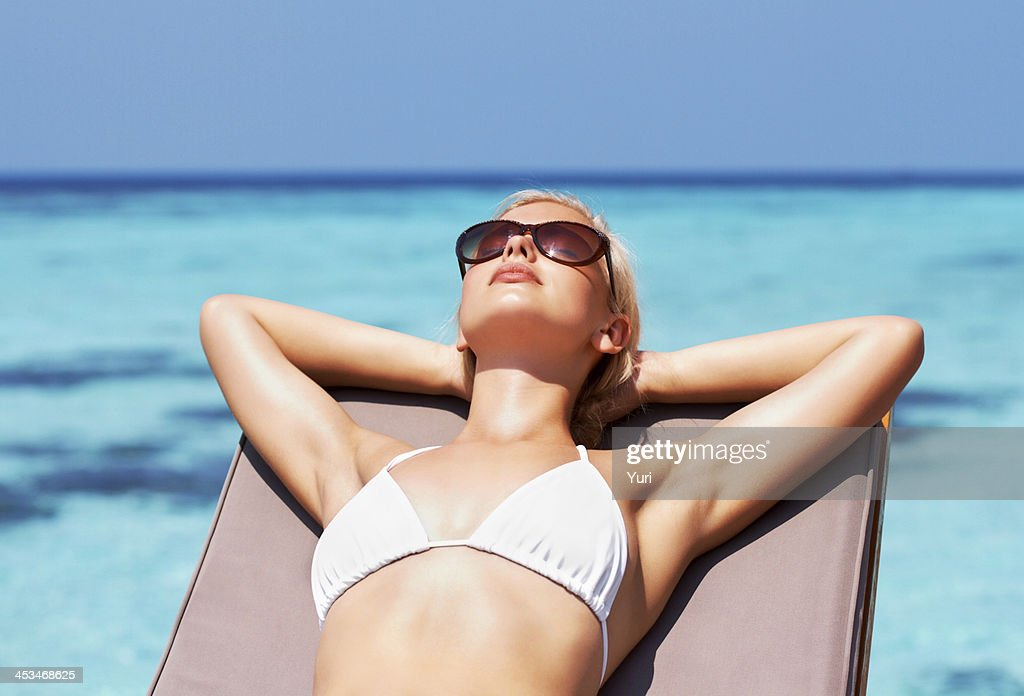 Young pretty girl sunbathing by the seaside : Stock Photo