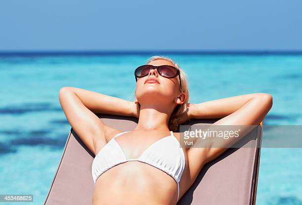Young pretty girl sunbathing by the seaside