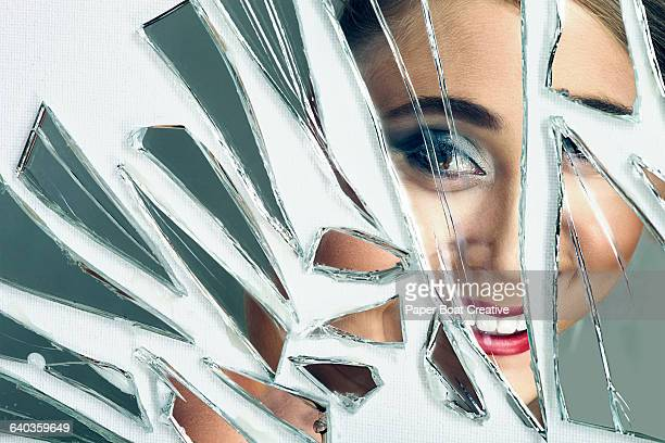 Young pretty lady smiling in to a broken mirror