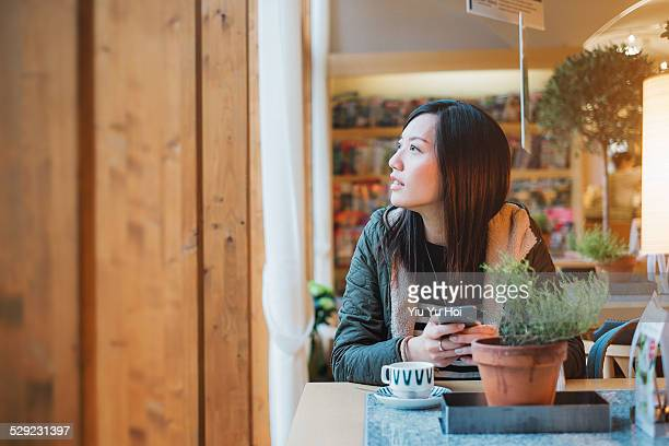 young pretty lady using her mobile phone in cafe - yiu yu hoi stock pictures, royalty-free photos & images