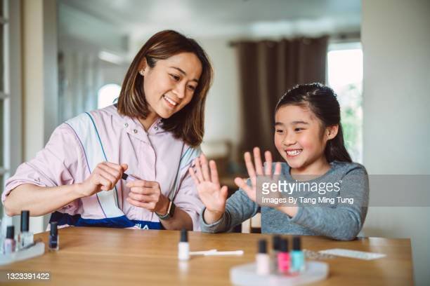young pretty mom polishing her daughter's fingernails at home joyfully - human finger stock pictures, royalty-free photos & images