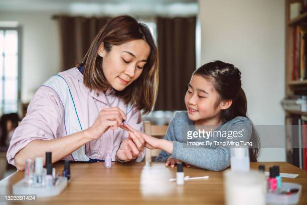 young pretty mom polishing her lovely daughter's fingernails at home joyfully - human finger stock pictures, royalty-free photos & images