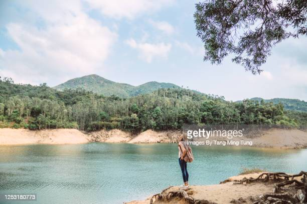 young pretty woman enjoying a scenic beautiful lake view joyfully while hiking on nature trail - aktiver lebensstil stock-fotos und bilder